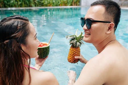 Happy young Asian boyfriend and girlfriend enjoying fruit ccktails and looking at each other when speding time in swimming pool