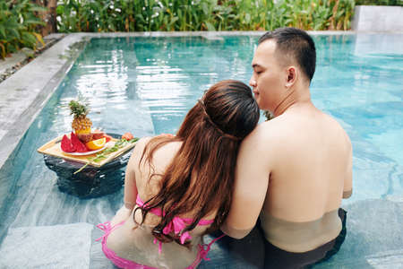 Young woman leaning on shoulder of her boyfriend when they are sitting in swimming pool and eating fresh fruits, view from the back
