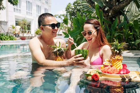 Happy young Vietnamese couple eating sweet delicious fruits for breakfast when refreshing in swimming pool