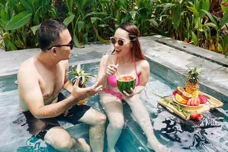 Positive young Asian couple sitting in swimming pool, eating tasty fruits and discussing plans for the day Stok Fotoğraf