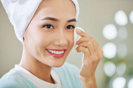 Smiling attractive young Vietnamese woman wiping off her make-up Reklamní fotografie