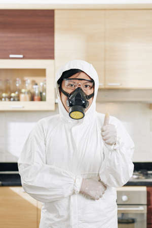 Portrait of professional cleaning service worker in protective hazmat suit standing in disinfected kitchen and showing thumbs-up