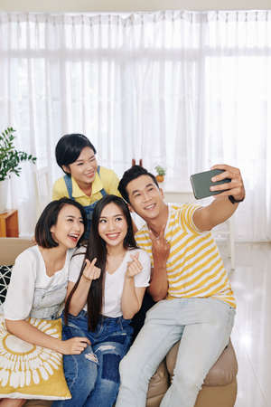 Group of joyful Vietnamese young people sitting on sofa at home and posing for selfie