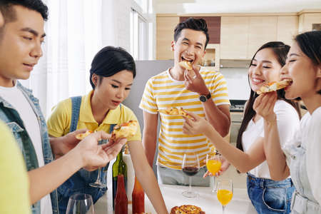 Group of happy young Asian people enjoying delicious pizza at house party