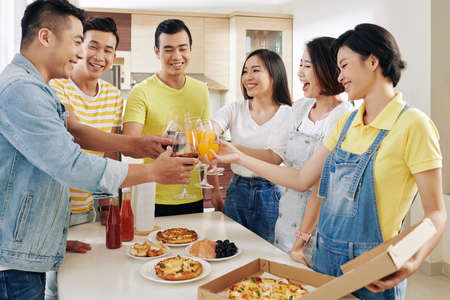 Cheerful friends toasting with glasses of juice over table with tasty pizza and snacks
