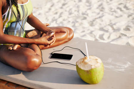 Cropped image of young fit Black woman sitting on chaise-lounge, drinking coconut water and listening to music in her smartphone