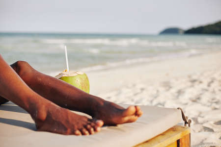 Cropped image of young Black woman resting on chaise-lounge and drinking refreshing coconut water on sea beach Reklamní fotografie