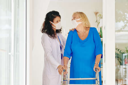 Caregiver in medical mask helping senior woman to move with help of walker Stock Photo
