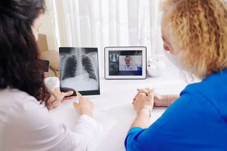 Senior patient visiting physician who is discussing chest x-ray with experienced pulmologist via video call Banque d'images