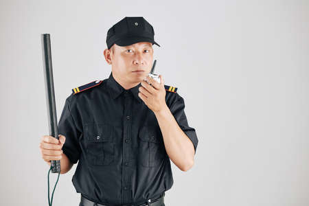 Studio photo of serious police officer raising hand with truncheon and talking to chief of police via walkie-talkie
