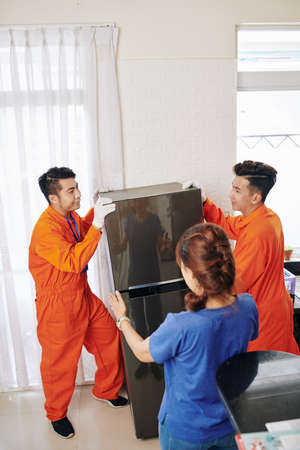 Unrecognizable woman telling delivery men where to put her fridge, vertical high angle shot, copy space