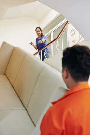 Moving men carrying big sofa upstairs, mature woman standing there directing them, vertical over-the-shoulder shot
