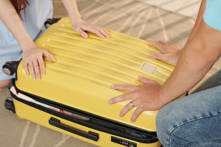 Close-up image of man and woman pushing suitcase cover when trying to fit in belongings