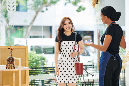 Female small shop owner holding door for happy pretty customer walking in Stock Photo