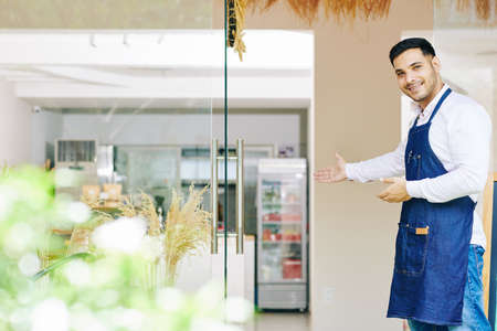 Smiling young Indian man in denim apron inviting customers in bakery he just opened