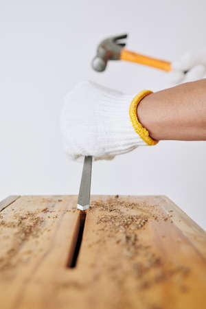 Carpenter in textile gloves using chisel and hammer when making hole in wooden bench