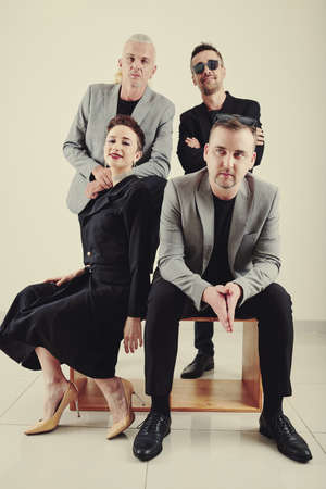 Male and female music band members sitting on wooden box when posing for placard