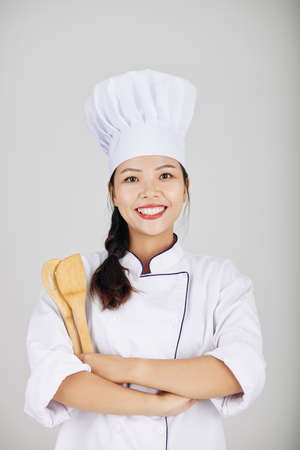 Portrait of confident young restaurant chef posing with wooden spatulas and smiling at camera