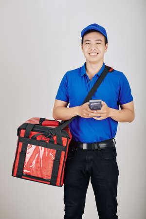 Portrait of smiling young Vietnamese courier with payment terminal and delivery bag Reklamní fotografie