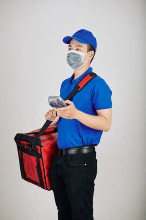 Express delivery service worker in medical mask with big food bag and payment terminal Reklamní fotografie