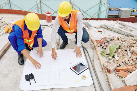 Engineers in hardhats discussing details of house blueprint when working at construction site