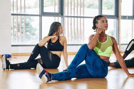 Fit Black young women doing spine twist pose when practicing yoga in studio