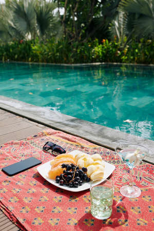 Plate with delicious fruits, glasses of cocktails and smartphone on blanket next to swimming pool Stok Fotoğraf