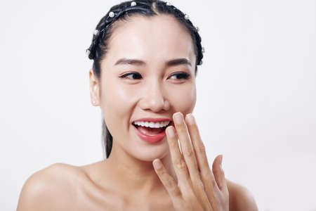 Happy beautiful young Asian woman laughing and covering her mouth with hand