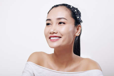 Studio portrait of beautiful young Vietnamese woman with toothy smile and flawless nude make-up