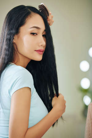 Beautiful young Asian woman brushing hair when getting ready in the morning
