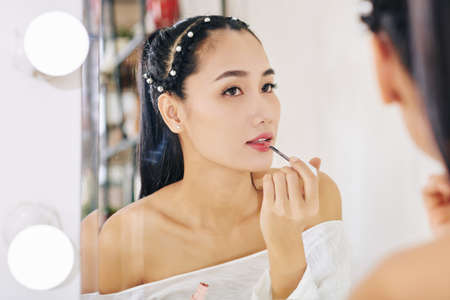 Attractive young Asian woman applying lip gloss in front of mirror when getting ready at her vanity