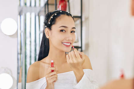 Portrait of smiling happy young Asian woman applying red liquid lipstick