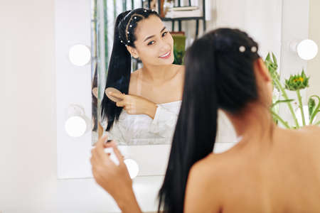 Smiling pretty young Asian woman brushing hair in front of vanity 版權商用圖片