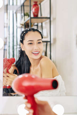 Happy beautiful young Asian woman blowing out hair when getting ready at her vanity