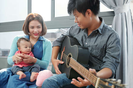 Vietnamese young man playing guitar and singing for his little daughter Standard-Bild