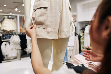 Young female customer touching fabric of beige shorts on mannequin in shopping mall