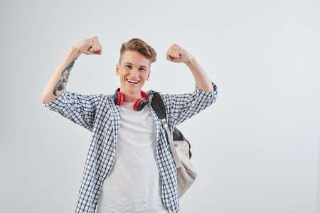 Excited smiling high school student raising arms and showing muscles feeling proud about his achievements Reklamní fotografie