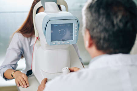 Ophthalmologist using modern equipment when checking eyesight of young female specialist