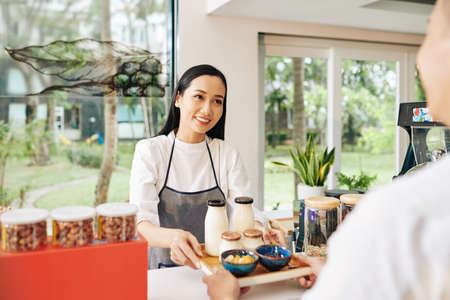 Small coffeeshop waitress giving tray with non-dairy yogurt, milk and bowls of cornflakes to customer