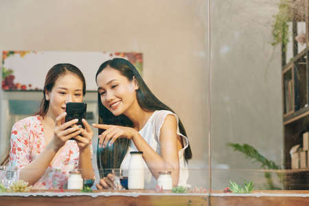 Beautiful young Vietnamese female friends checking photos they just made on smartphone