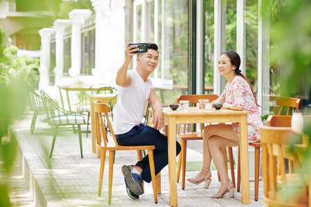Handsome young Vietnamese man taking selfie when eating breakfast with girlfrind in outdoor cafe