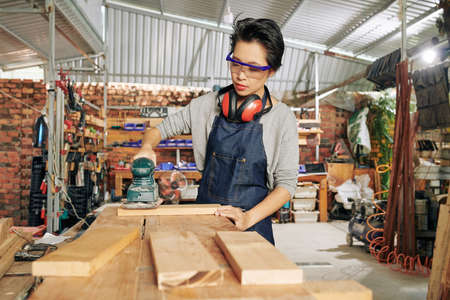 Young female carpenter in protective glasses polishing wooden plank using cordless sander
