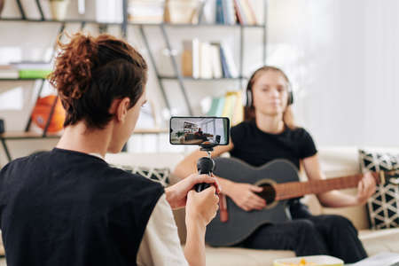Teenage boy using smartphone when shooting his friend playing guitar and singing for some contest