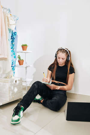 Depressed teenage girl sitting on the floor in her closet, listening to music in headphones and writing in her diary
