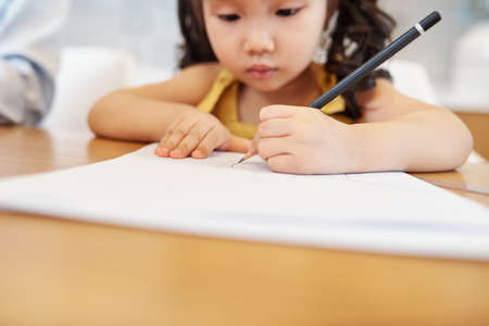 Serious little Asian girl drawing with pencil on white sheet, selective focus