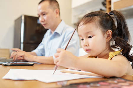 Little Vietnamese girl enjoying drawing with pencil when sitting at table next to her father busy with work on laptop Zdjęcie Seryjne