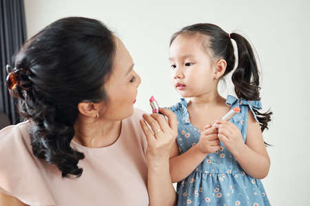 Curious adorable little Vietnamese girl looking at her mother applying light pink lipstick when getting ready in the morning Stockfoto