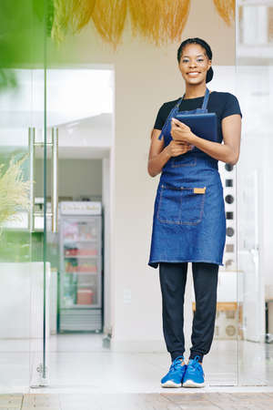 Portrait of pretty smiling young Black woman in denim apron holding tablet computer when standing at entrance of her cafe