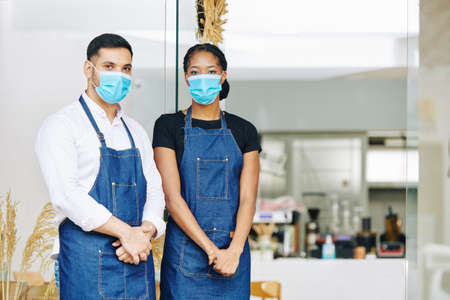 Young waiter and waitress in medical masks and aprons standing at entrance of small bakery