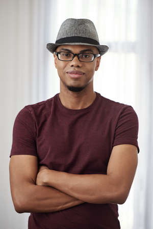 Portrait of handsome smiling young Black man in fedora hat and glasses crossing hands and smiling at camera Фото со стока